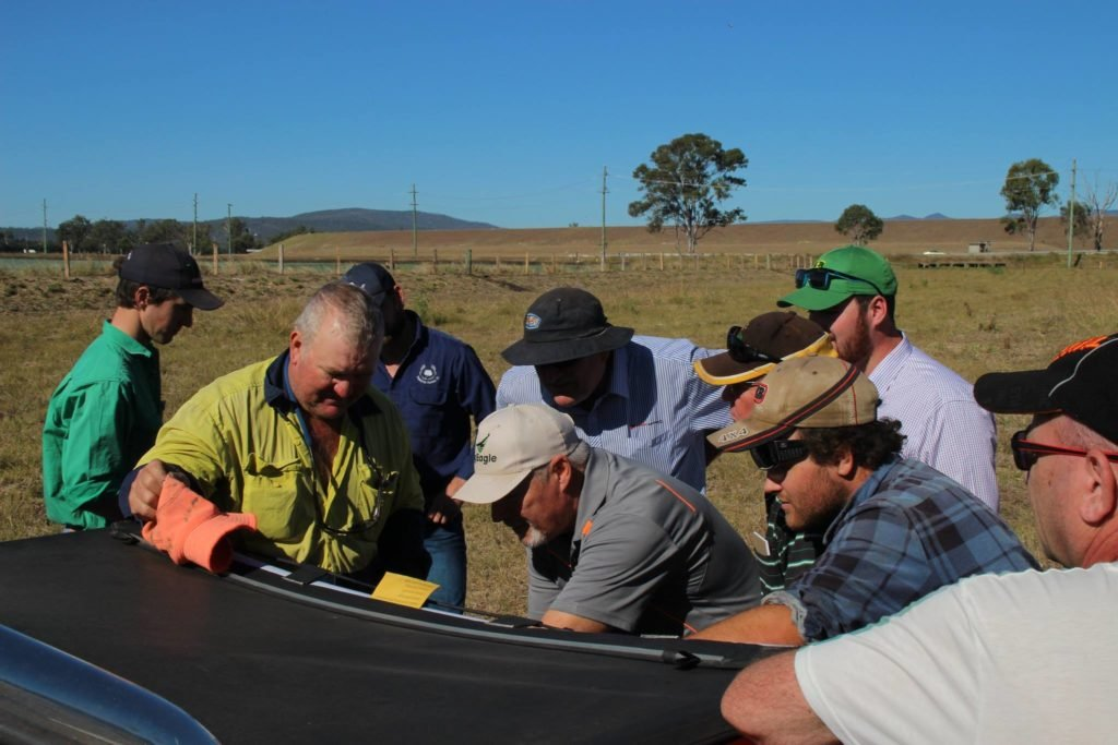 Farmers gather around the laptop at the Laidley agricultural drone demo to see what the UAV is capturing